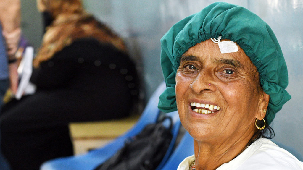 A woman wearing surgical gown and hat smiles before her eye surgery.