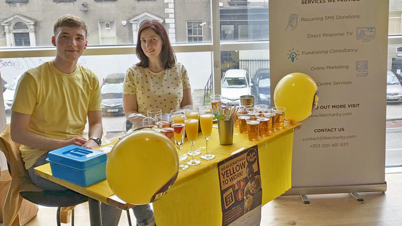Two staff from LikeCharity with a yellow table full of drinks.