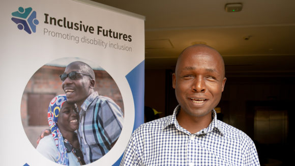 Deus Turyatemba stands next to an Inclusive Futures poster