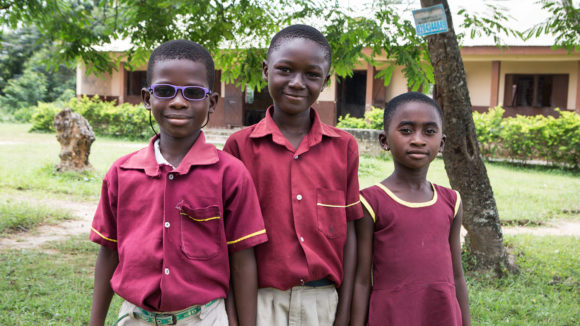 Three school children from Ghana smiling outside their school.