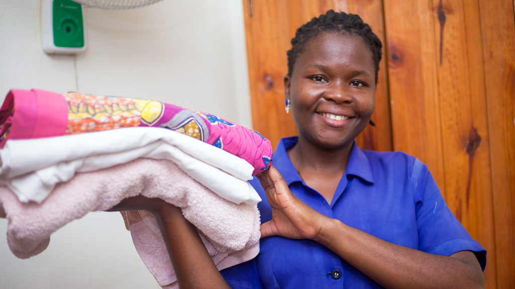 Grace holds a pile of folded linen and smiles at the camera.