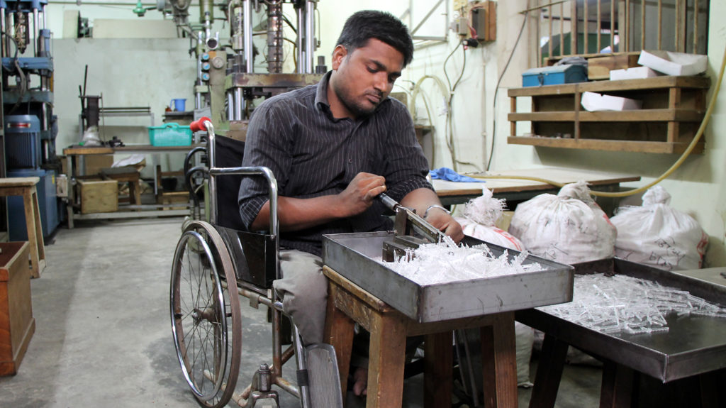 A man in a wheelchair works in a workshop in Dhaka.