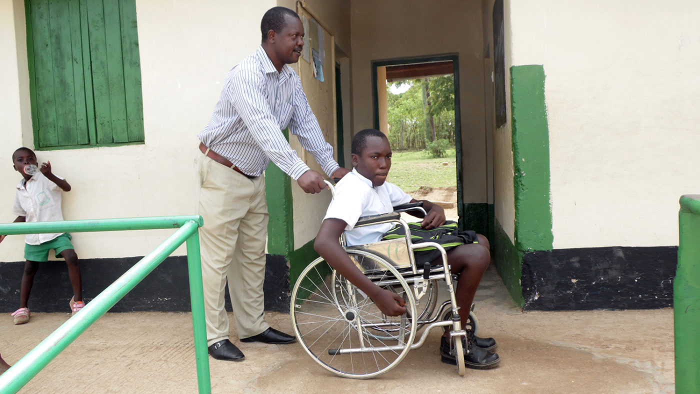 A student in a wheelchair is pushed by a teacher at a school in Kenya.