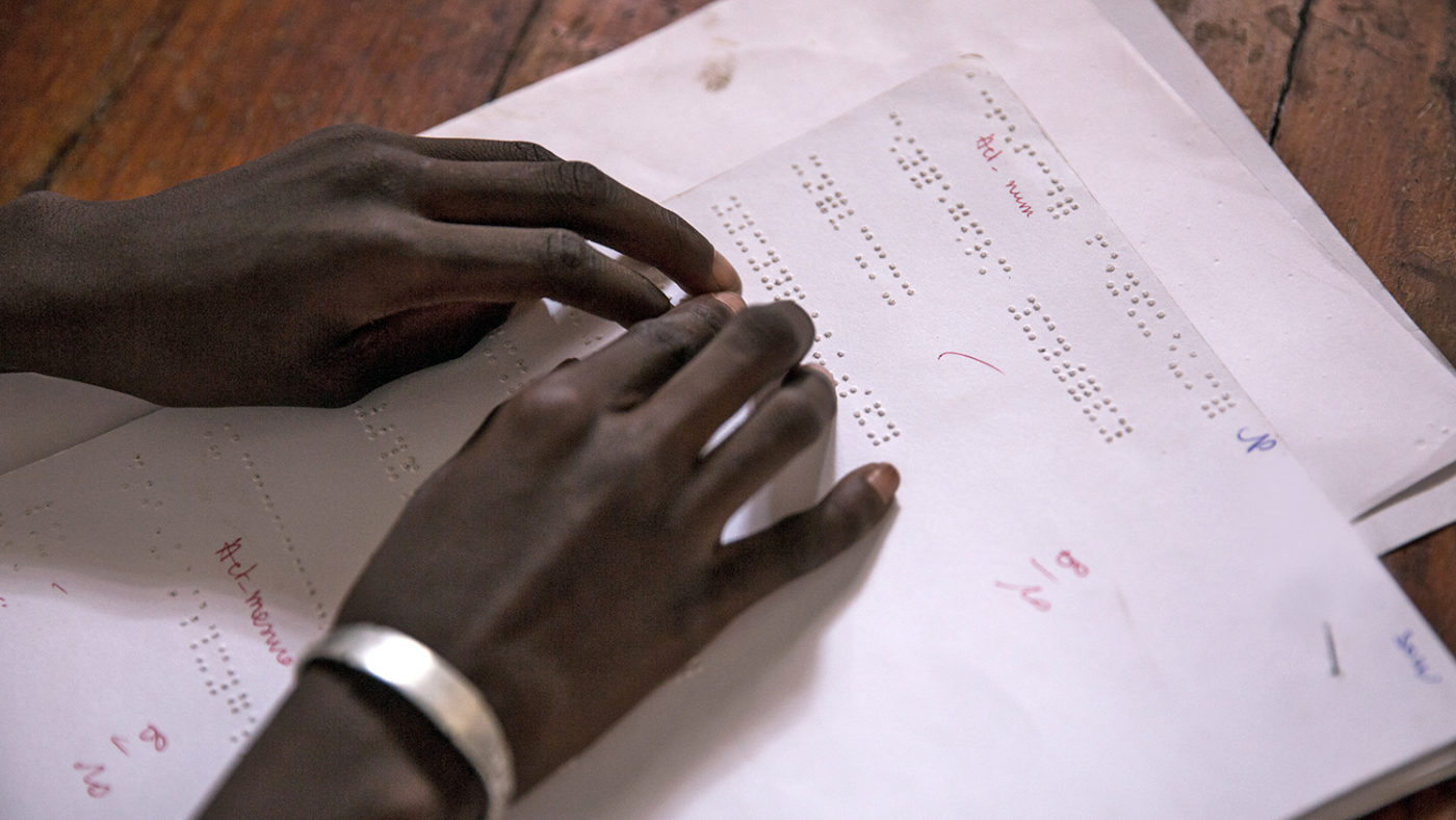 A girl from Senegal reads braille in the classroom.