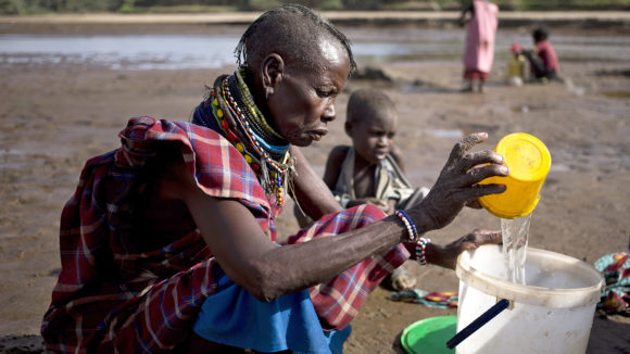 A woman from Turkana in Kenya pours water into a bucket on the banks of a river.