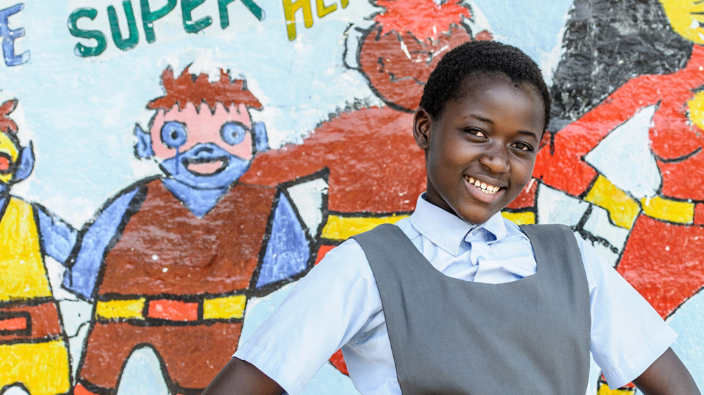 A school student in Zambia stands in front of a mural depicting superhero characters from Sightsavers' Super School of 5 programme.