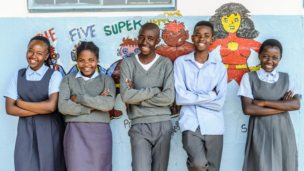 Five school students in Zambia in front of a mural depicting superheroes from Sightsavers' Super School of 5 programme.