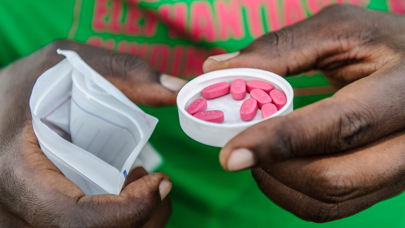An eye health worker holding some pink tablets.