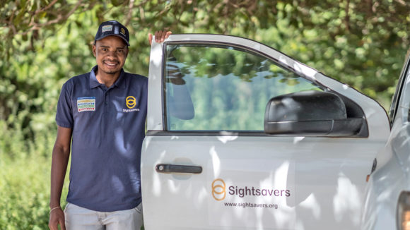 An eye health worker wearing a purple t-shirt with the People's Postcode Lottery and Sightsavers logos, standing next to a van with the Sightsavers logo on the door.