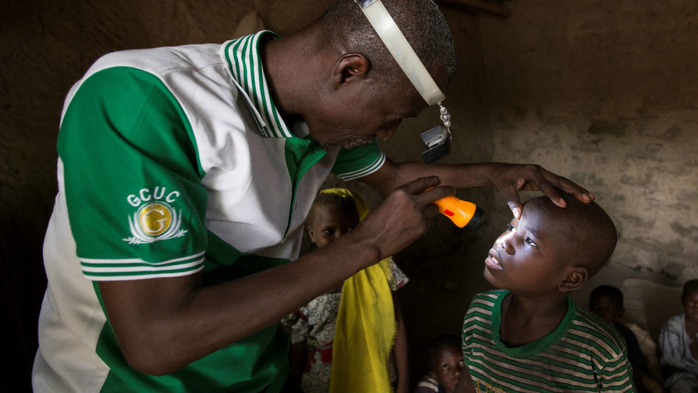 Checking a childs eyes at a routine house visit in Nigeria