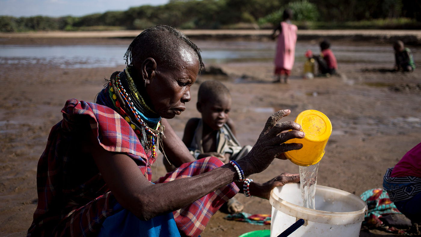 A woman pours water that she has collected from a river into a bucket