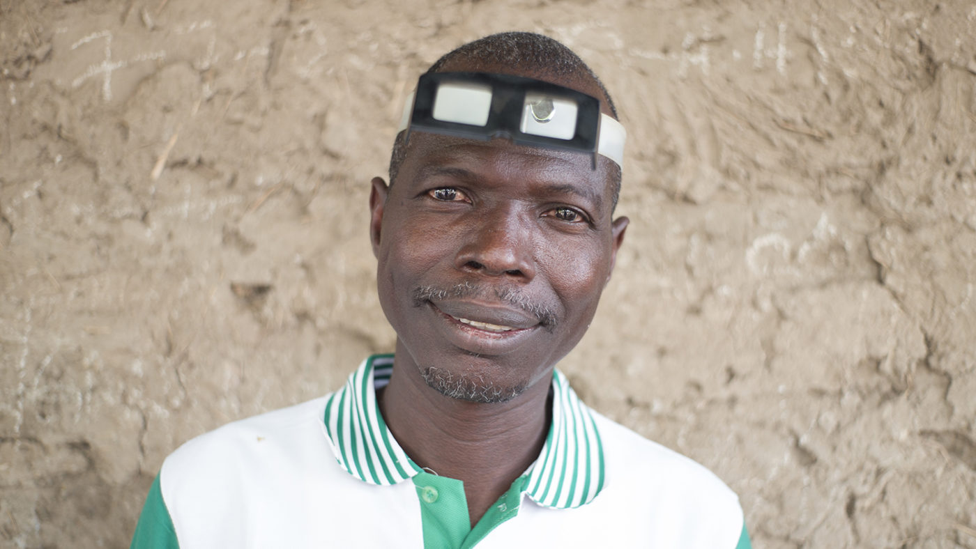 Aliyu, a trachoma surgeon from Nigeria, smiling and wearing eye-examination spectacles on his head.