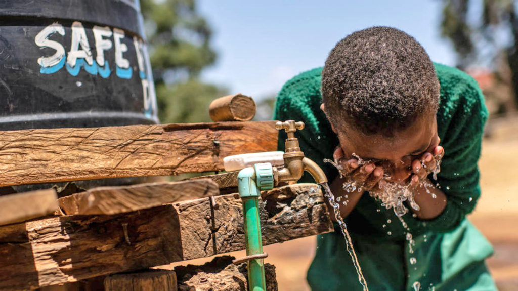 A boy washes his face using water from a tap.