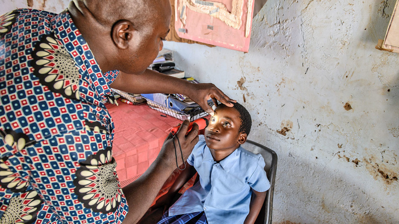A doctor carries out a home visit to check Gladys's eyesight