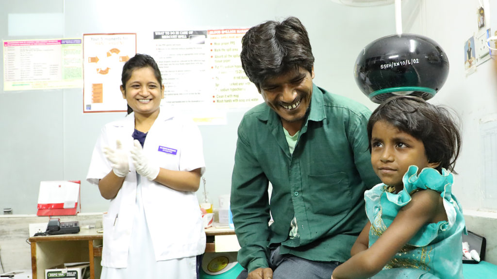Rukmani sits in hospital after her cataract operation. Her father and a nurse smile behind her.