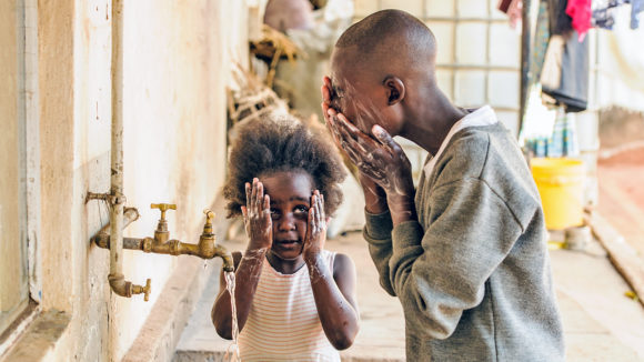 In Zambia, a boy teaches his sister how to wash her face to prevent trachoma.
