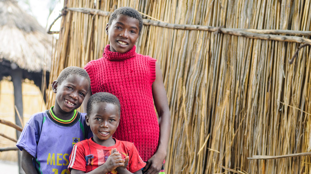 Three siblings from Zambia smile following their trachoma treatment.
