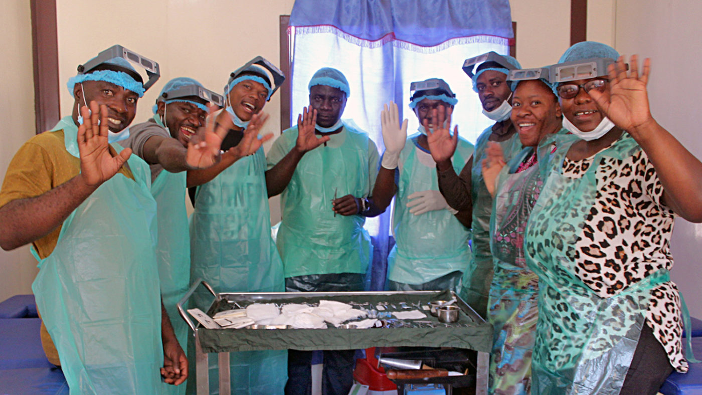 A group of trachoma surgeons in Zambia wearing scrubs and smiling.