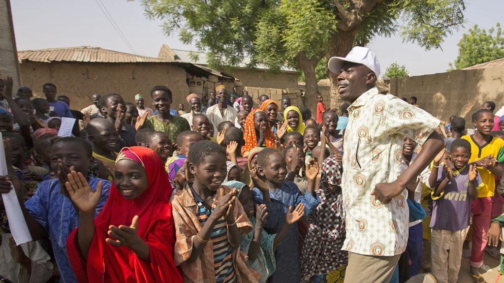 Alioyu, a trachoma surgeon in Nigeria, dances to keep the children amused.