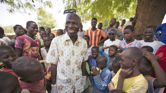 Sightsavers surgeon Aliyu smiles with a group of children.