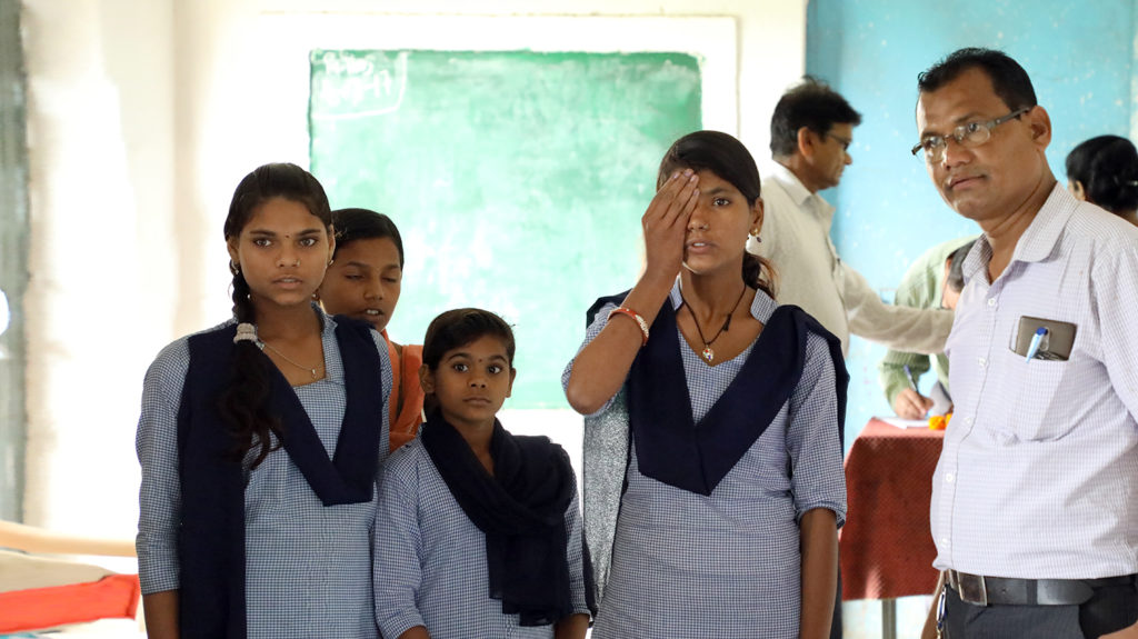 A student covers one eye during an eye test at a school in India.