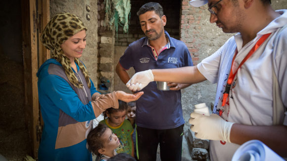 A local health worker hands medication to a woman as another health worker looks on.