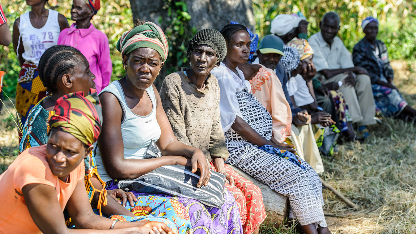Patients in Zambia sit in lines in the sunshine, waiting to be screened for trachoma.