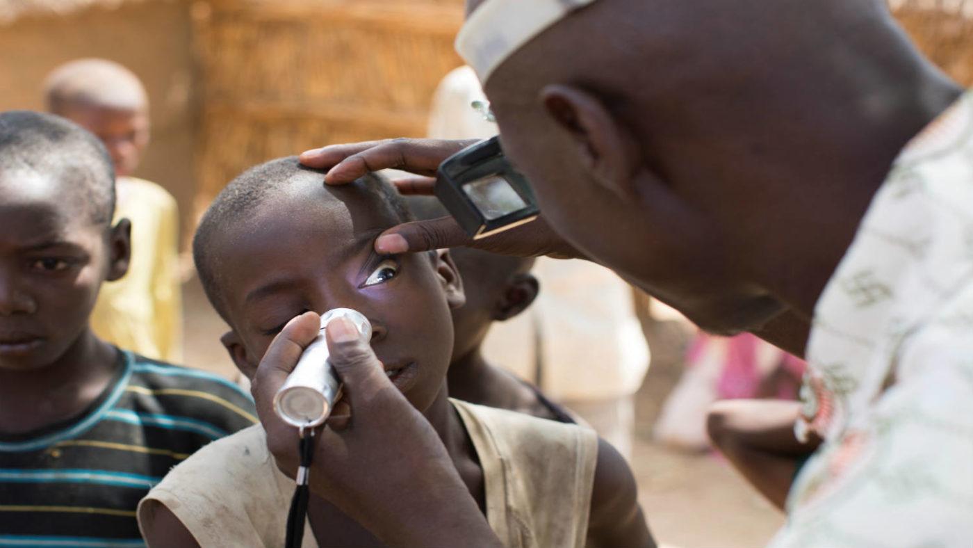 Trachoma surgeon checking eye sight of boy in Nigerian village