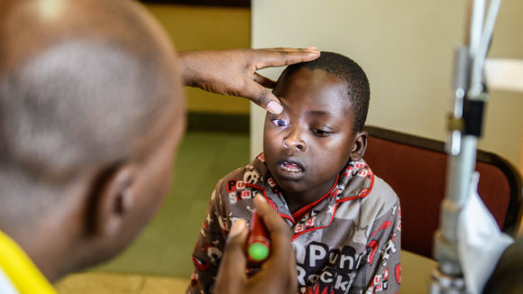 Dr Celestin Habiyakare checking Lovemore's eyes