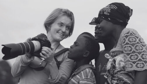 Kate Holt holding her camera and showing the screen to two smiling African children.