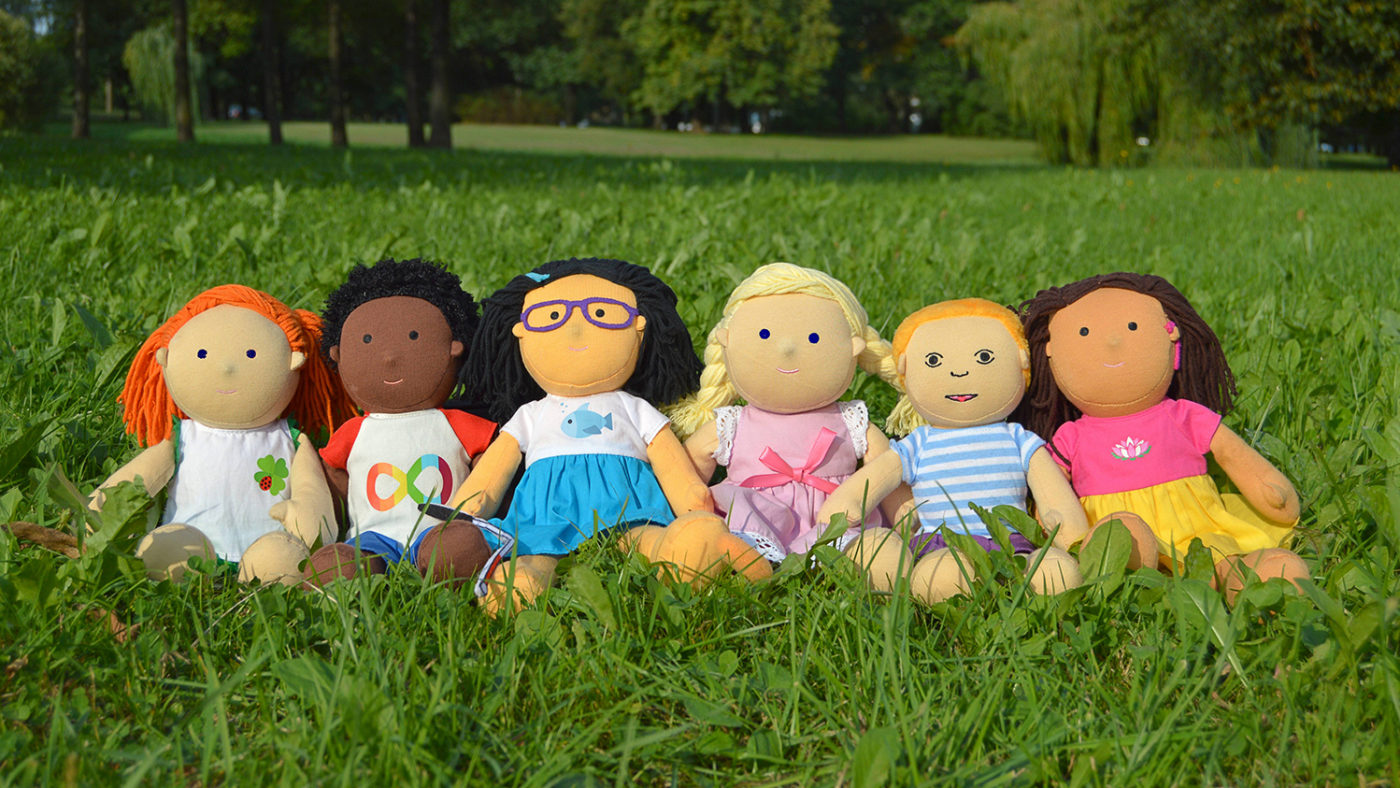 Six children's dolls lined up in a field
