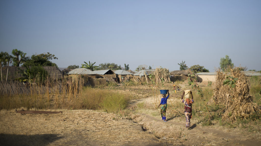 A scene from Kaduna in Nigeria, showing a dry, dusty landscape with sparse greenery. Two women carry water on their heads.