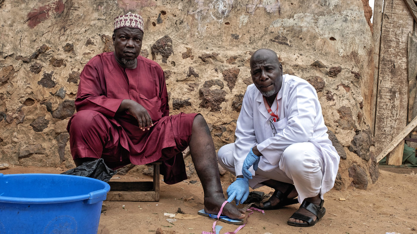 Muhammed, who has lymphatic filariasis, with health worker Suraji in Nigeria.