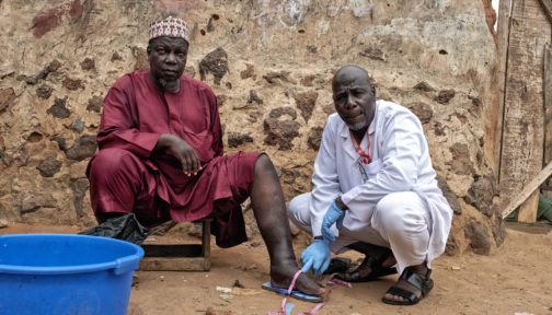 Muhammed, who has lymphatic filariasis, with health worker Suraji in Nigeria.