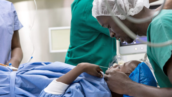 A child lies on the operating table while an eye health worker checks.