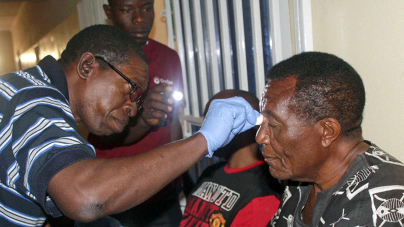 An eye health worker checks a man's eyes.