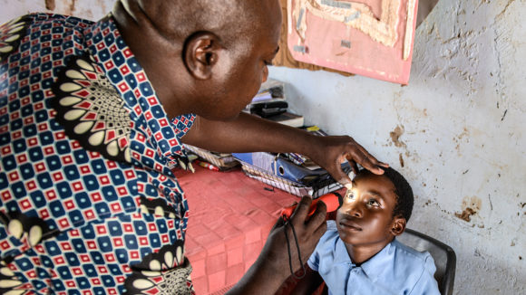 Ophthalmic nurse Postan Phiri examines a child's eyes in Zambia.