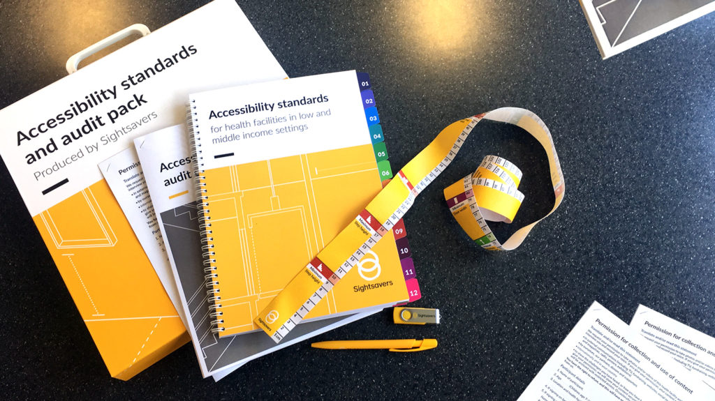 The contents of the accessibility audit pack spread on a table, including the accessibility standards, checklist, a tape measure, pen and USB stick.