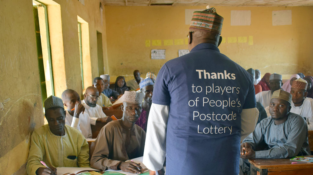 A trainer teaches a classroom of teachers about eye care. He wears a T-shirt saying 'Thanks to players of People's Postcode Lottery'.