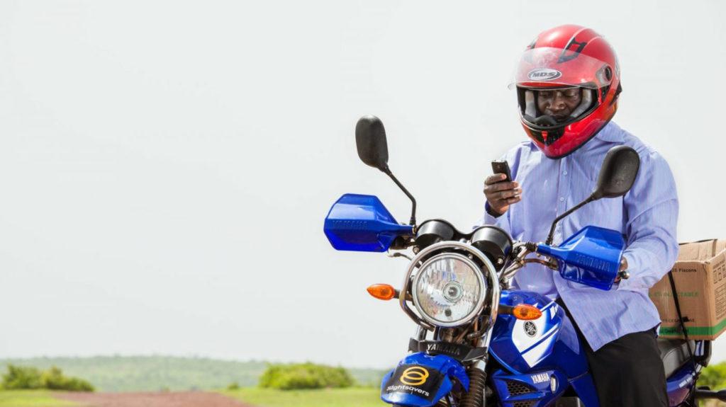 Surgeon Yanoussi Ouologuem distrbuting medication on motorbike.