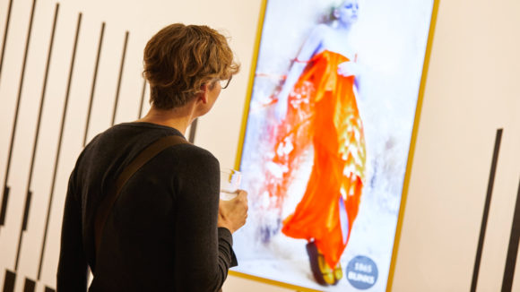 Lady looking at degrading image in art gallery