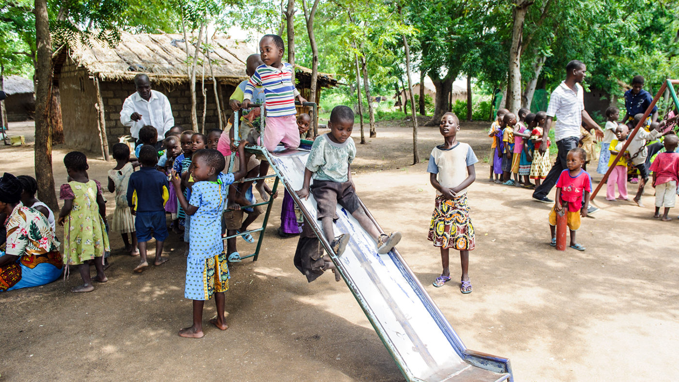 Children line up to go down a slide.