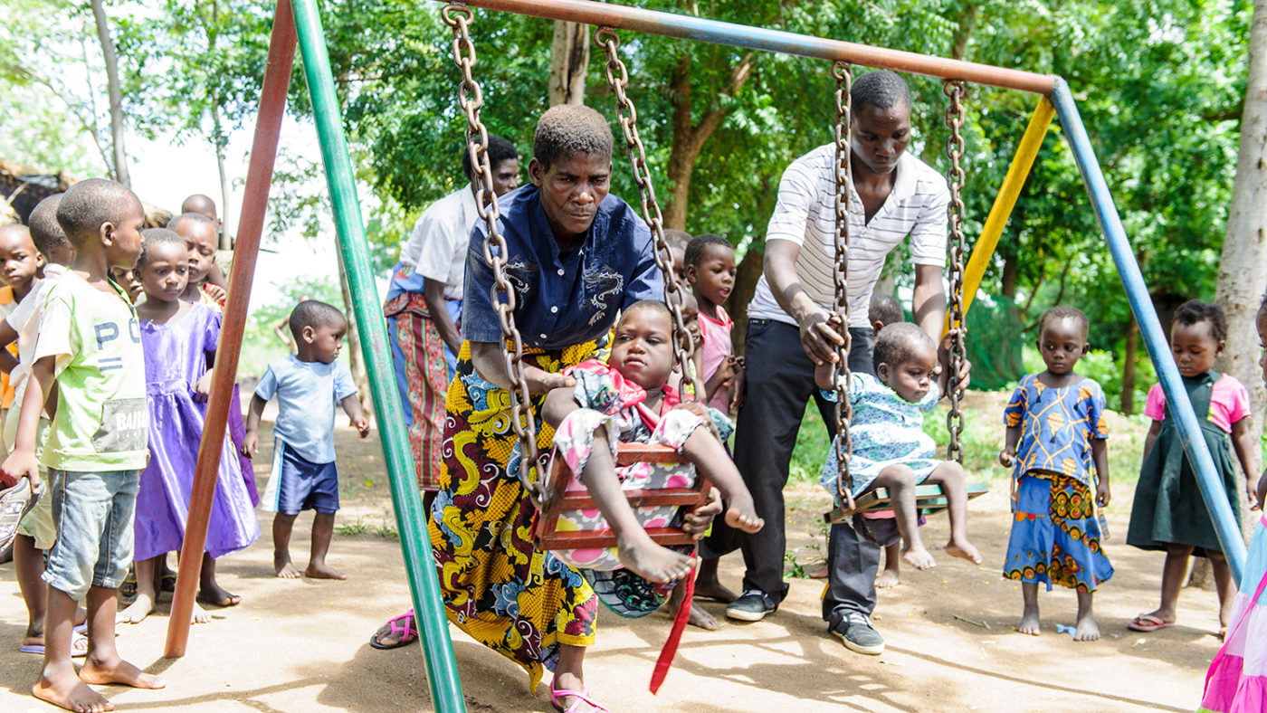 A women pushes a child on swings.