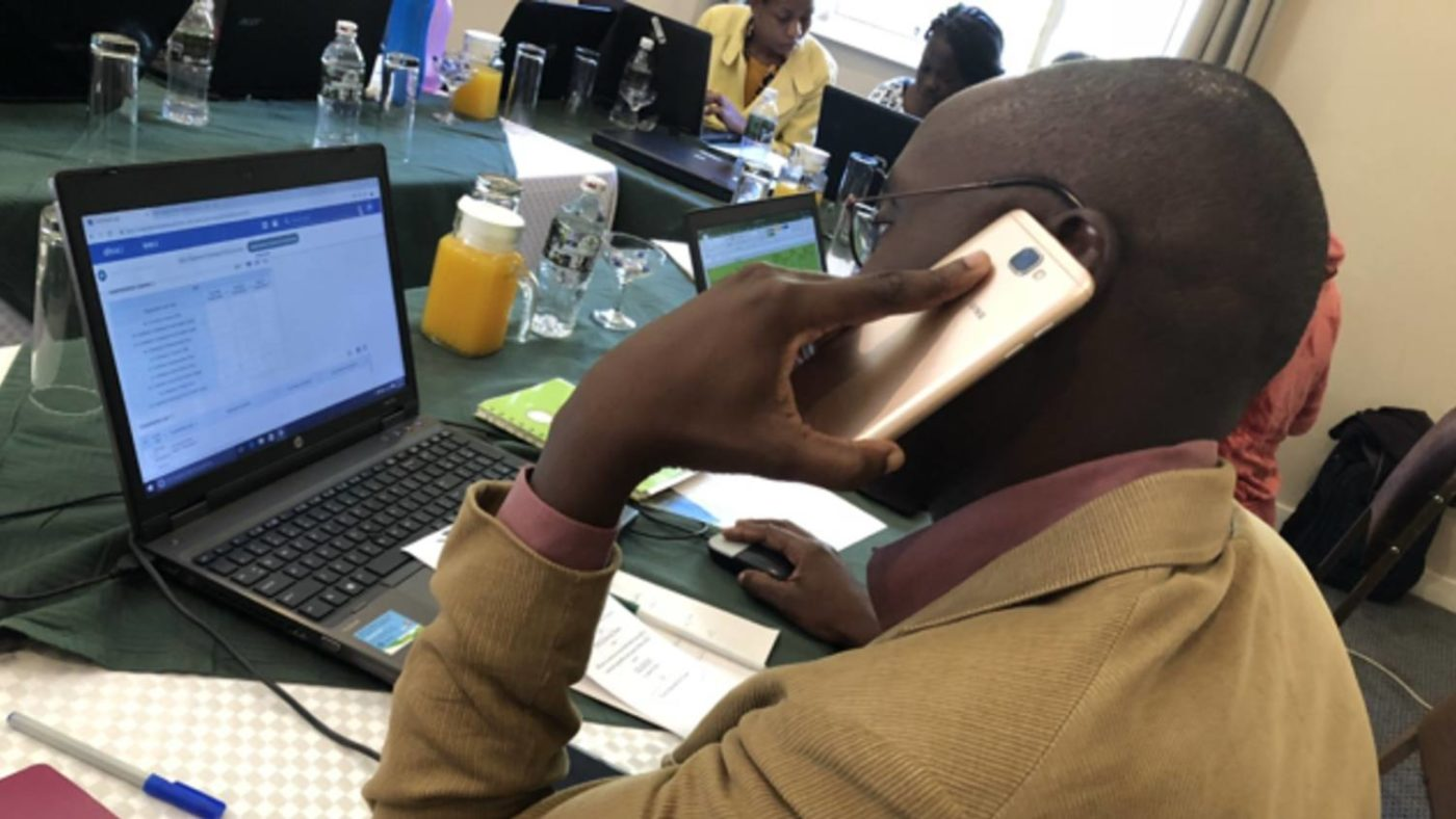 A man enters data onto a computer and speaks on the phone at the Command Centre for trachoma MDA in Zimbabwe