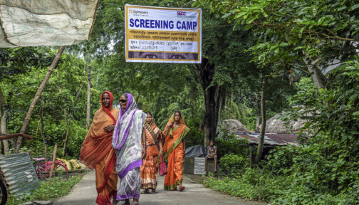 A group of women walk underneath a Sightsavers sign which reads: Screening camp.