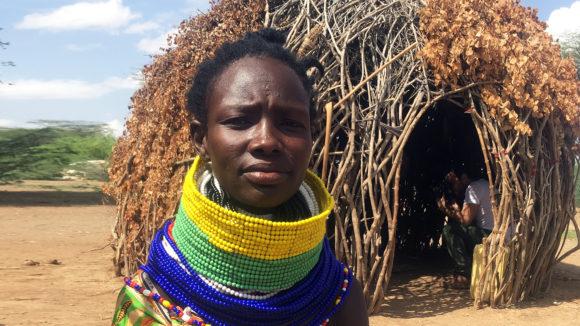 A lady sits outside in rural Kenya.