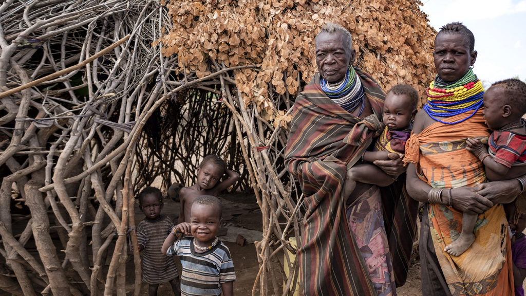 Two women and five small children stand outside their home.