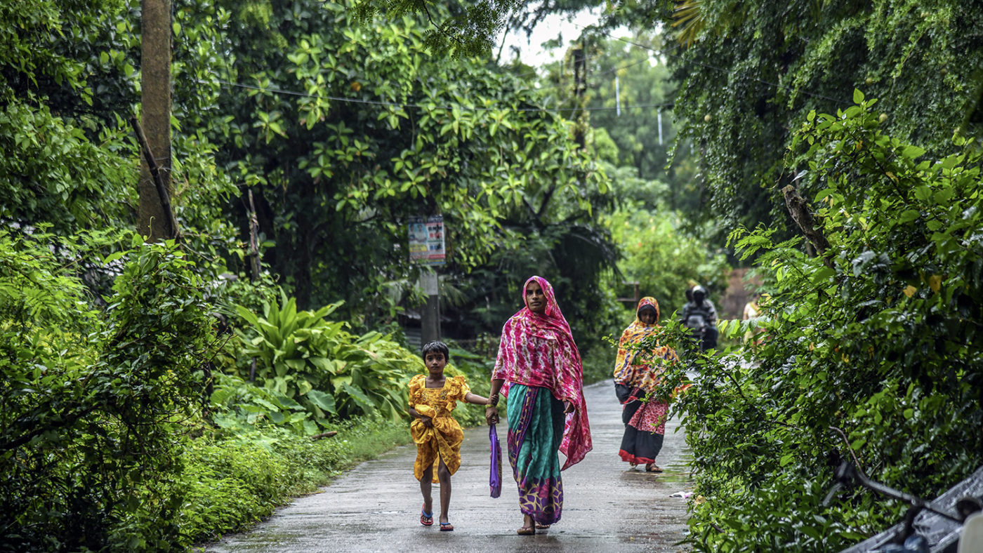 A women and a child walk on a wet path under trees.