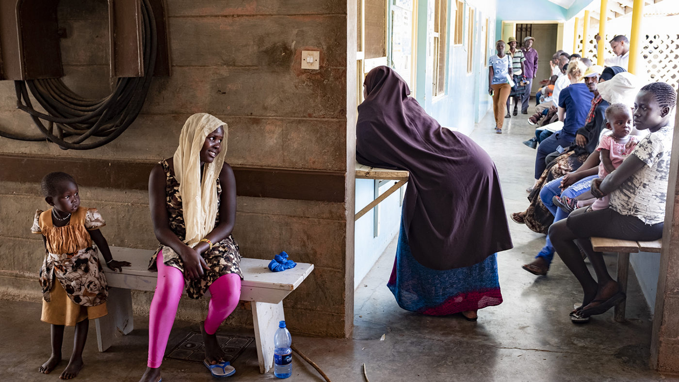 A women leans against a reception desk at a health clinic.