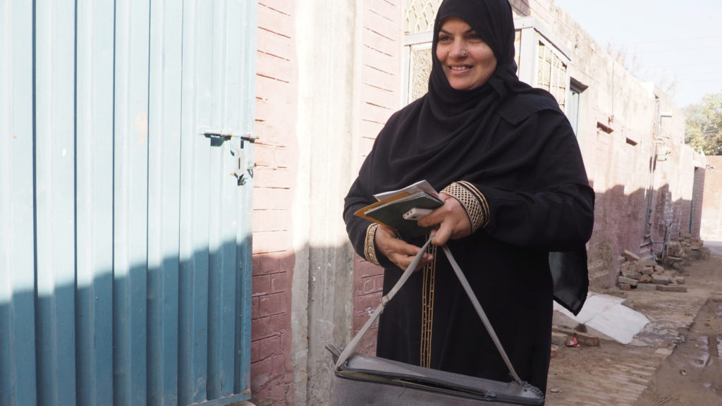 A woman wearing a black hijab smiles and walks along a brick-lined street.